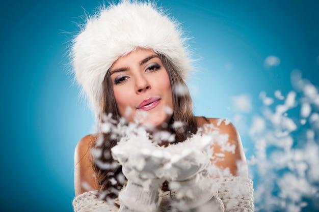 Schöne winterfrau, die schnee bläst