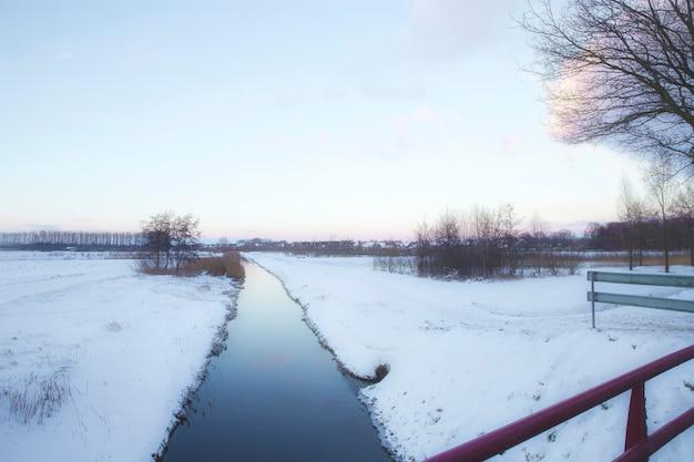 Schöne winterlandschaft bei sonnenuntergang mit nebel und schnee bedeckt ackerland und fluss niederlande