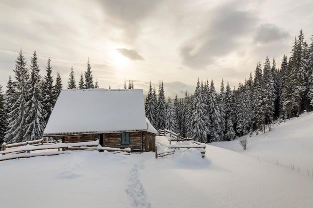 Schöne winterlandschaft. hölzerne schäferhütte auf gebirgsschneebedeckter reinigung unter kiefern auf kopienraum des bewölkten himmels. frohes neues jahr und frohe weihnachten-karte.