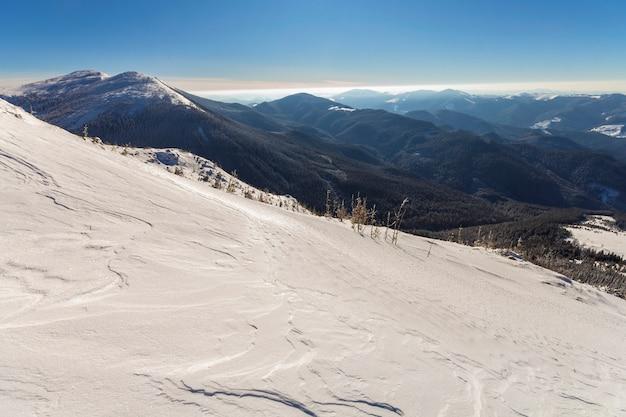 Schöne winterlandschaft. steile gebirgshügelsteigung mit weißem tiefem schnee, entferntem waldigem gebirgszugpanorama, das zum horizont und zu den hellen strahlen der glänzenden sonne auf blauem himmel ausdehnt