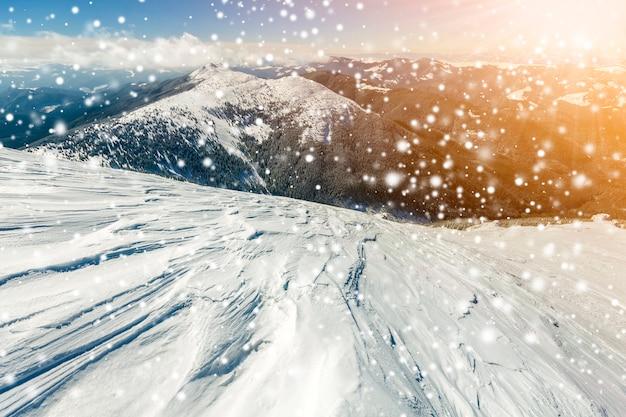 Schöne winterlandschaft. steiler berghanghang mit weißem tiefschnee, entferntem gebirgspanorama, großen schneeflocken und strahlenden sonnenstrahlen auf buntem kopierraum des blauen himmels.