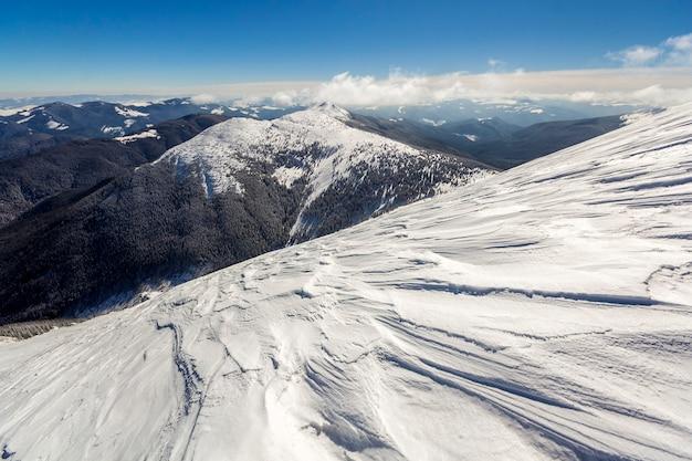 Schöne winterlandschaft. steiler berghanghang mit weißem tiefschnee, entferntem waldreichem gebirgspanorama, das sich bis zum horizont erstreckt, und hell leuchtenden sonnenstrahlen auf blauer himmel kopieren raumwand.