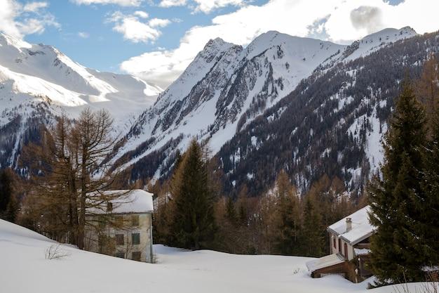 Schöne winterlandschaft. zwei gebäude unter hohen grünen fichten von den steilen waldigen bergen bedeckt mit weißem tiefem schnee unter hellem blauem himmel am sonnigen eisigen tag.