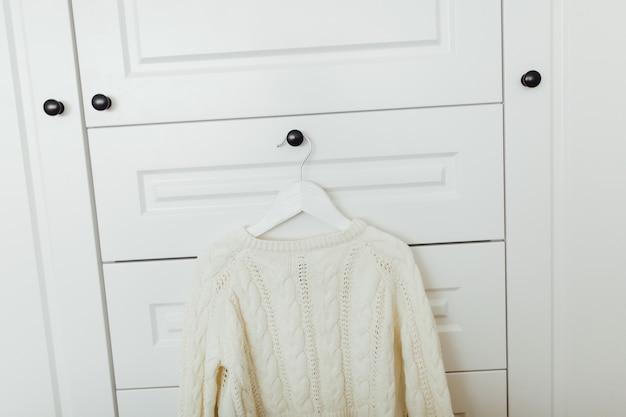 Schöne winterstrickjacke für mädchen auf aufhänger am hintergrund der weißen garderobe