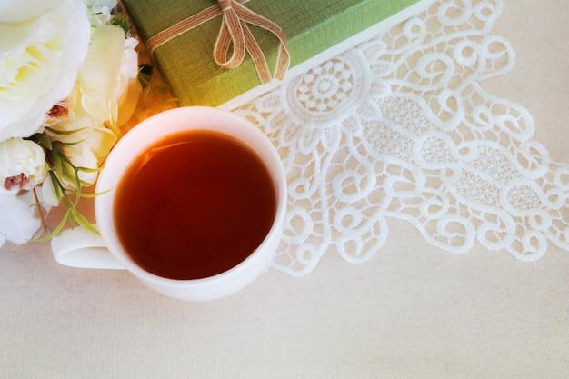 Schöne wohnung legen eine tasse tee mit spitzendekorationen für hochzeitshintergrund