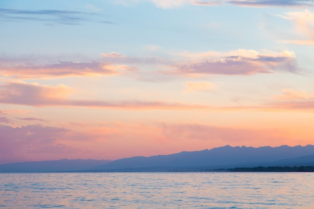 Schöne wolken über dem meer. berge im hintergrund