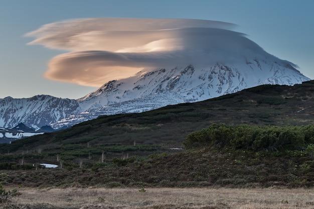 Schöne wolken über dem vulkan bei sonnenuntergang