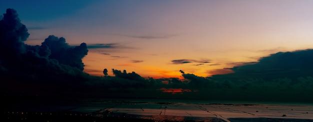 Schöne wolkenlandschaft und dunkler dramatischer sonnenuntergangshimmel am strand