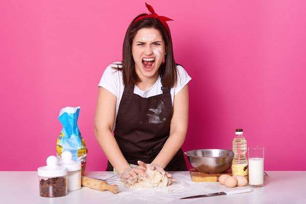 Schöne wütende köchin knetet teig und schreit laut, krank und müde von der zubereitung von hausgemachtem gebäck. wütende brünette frau arbeitet in der küche und träumt von ruhe. kulinarisches und lebensmittelkonzept.