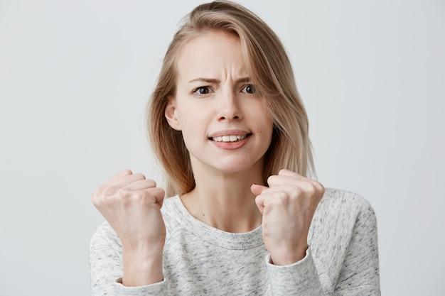 Schöne wütende wütende europäische frau, die sich lässig gekleidet fühlt, runzelt unzufrieden die stirn, hält die fäuste geballt, bereit, sich zu schützen und zu kämpfen, fühlt sich beleidigt. negative emotionen