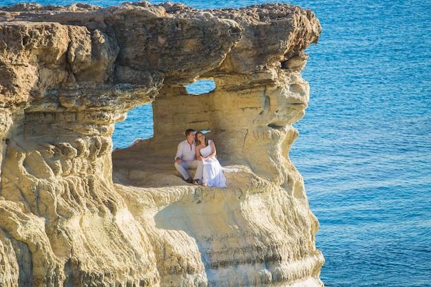 Schöne wunderschöne braut und stilvoller bräutigam auf felsen, auf dem hintergrund eines meeres, hochzeitszeremonie auf zypern