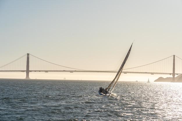 Schöne yacht in der bucht von san francisco bei sonnenuntergang, golden gate bridge am horizont