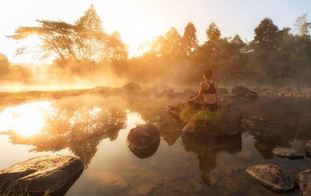 Schöne yogafrau morgens am park der heißen quelle.