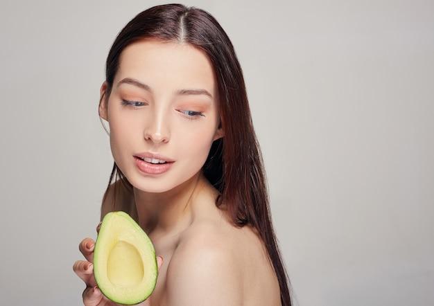 Schöne zarte dame mit reiner haut mit avocado in der hand