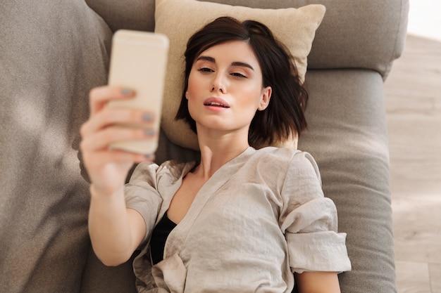 Schöne zarte frau im gewand, die am morgen freizeit zu hause verbringt und selfie macht, während sie im bett liegt