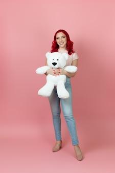 Schöne, zarte frau in voller länge in jeans mit roten haaren umarmt einen großen weißen teddybär