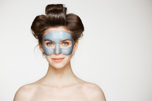 Schöne zarte nackte frau in den lockenwicklern und im lächeln der gesichtsmaske. beauty health kosmetologie und hautpflege.