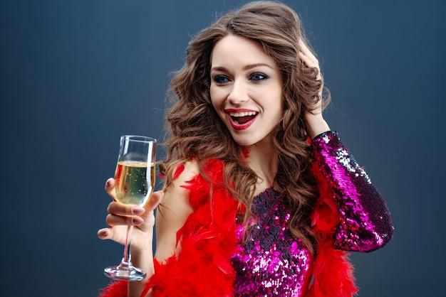 Schöne zauberfrau, die glas champagner halten feiert
