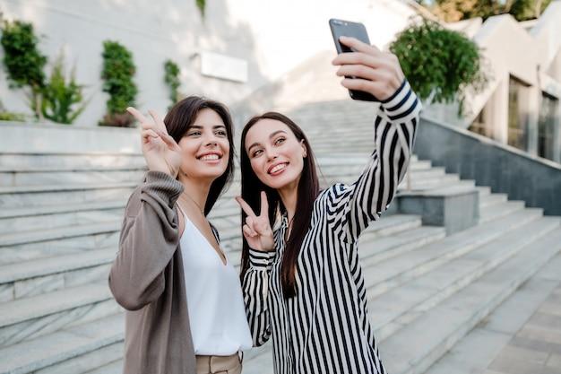 Schöne zufällige frauen, die draußen selfie in der stadt machen