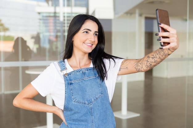 Schöne zufriedene frau, die selfie mit smartphone nimmt