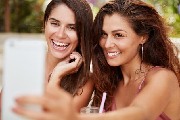 Schöne zufriedene frau mit attraktivem aussehen hat angenehmes lächeln, hält smartphone, sitzt in der nähe der besten freundin