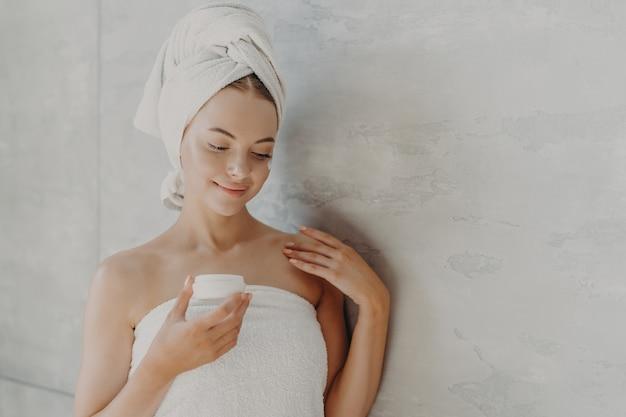 Schöne zufriedene frau mit gesunder haut minimales make-up trägt gesichtscremeständer in badetuch gewickelt auf
