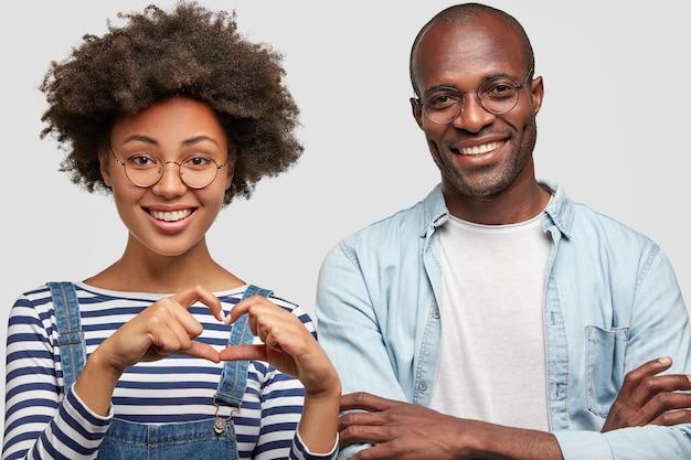 Schöne zufriedene lockige junge afroamerikanerin macht herzgeste, drückt liebe und gute einstellung aus, steht neben ihrem fröhlichen dunkelhäutigen freund und ist während des dates gut gelaunt