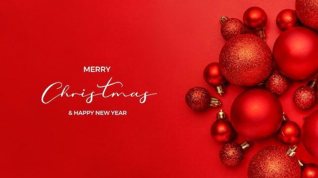 Schöne zusammensetzung der roten weihnachtskugeln auf rotem hintergrund