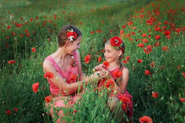 Schöne zwei mädchen im roten kleid, die im sommer auf mohnfeld gehen