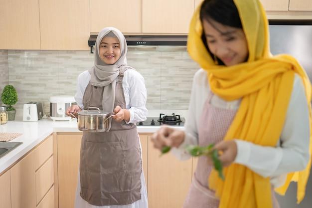 Schöne zwei muslimische frau genießen das gemeinsame abendessen für iftar, der das fasten auf ramadan in der küche bricht