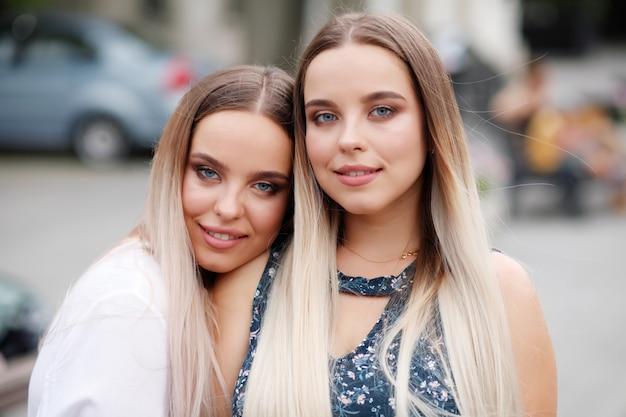 Schöne zwei zwillingsschwestern, die sich umarmen