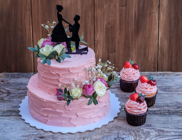 Schöne zweistufige hochzeitstorte mit rosa käsecreme, verziert mit lebenden rosen und einer figur eines verliebten paares, auf einem holztisch mit cupcakes