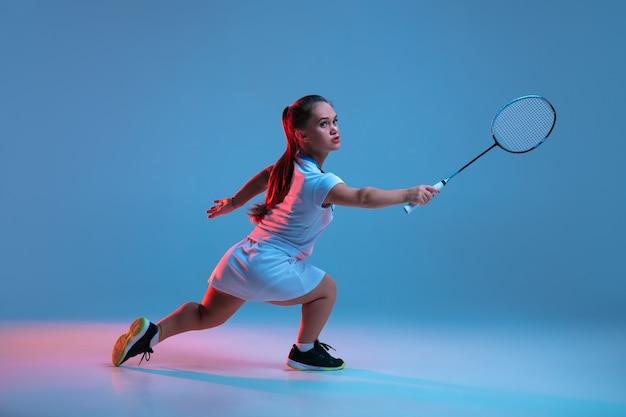 Schöne zwergfrau, die im badminton übt, lokalisiert auf blauem hintergrund im neonlicht