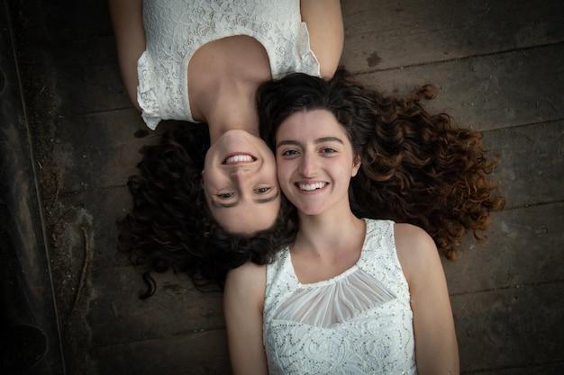 Schöne zwillingsschwestern in den weißen kleidern lächelnd und auf bretterboden liegend