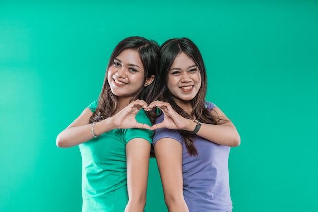 Schöne zwillingsschwestern zeigen ein herz von ihren händen auf einem grünen hintergrund.