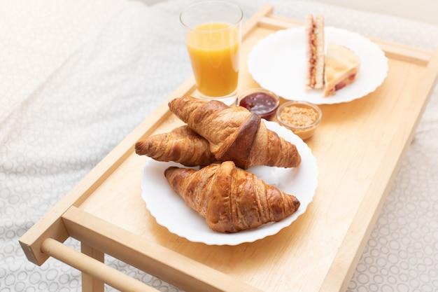 Schönen morgen. leckeres frühstück im bett - frische croissants, orangensaft, erdnussbutter und himbeermarmeladen-sandwich.