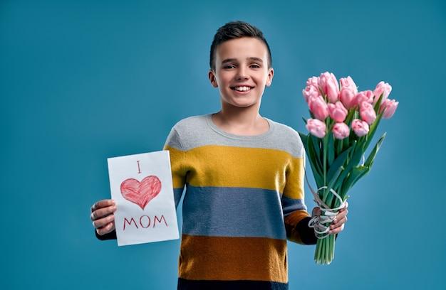 Schönen muttertag! ein gutaussehender junge in einem gestreiften mehrfarbigen pullover hält einen strauß tulpenblumen und eine postkarte für seine mutter isoliert auf blauem hintergrund.