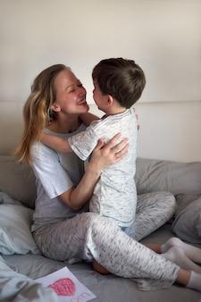 Schönen muttertag. kinderjunge gratuliert mama und gibt ihr blumentulpen und postkarte. mama und sohn lächeln und umarmen sich. familienurlaub und zweisamkeit. grußkonzept zum muttertag.