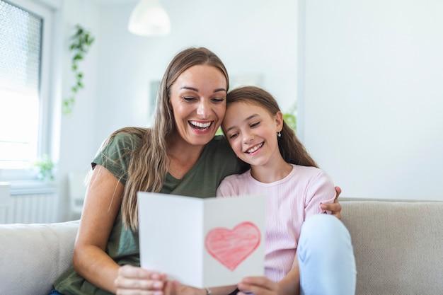 Schönen muttertag! kindertochter gratuliert mama und gibt ihre postkarte. mama und mädchen lächeln und umarmen. familienurlaub und zweisamkeit.