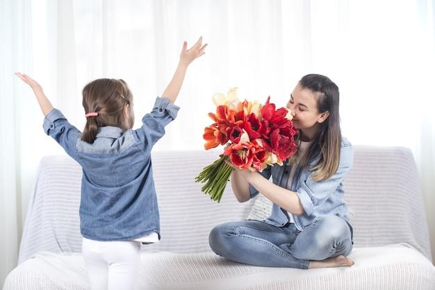 Schönen muttertag. kleine süße tochter mit einem großen strauß tulpen gratuliert ihrer mutter. im inneren des wohnzimmers das konzept eines glücklichen familienlebens