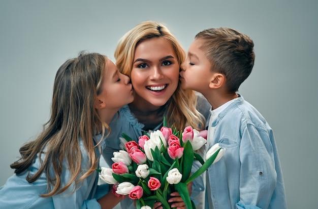 Schönen muttertag! nettes charmantes mädchen und junge geben ihrer schönen mutter einen strauß tulpenblumen und küssen auf den wangen, die auf einer grauen wand isoliert werden.