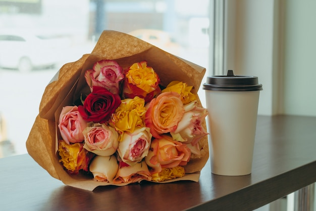 Schönen strauß frischer rosen in kraftpapier und kaffee zum mitnehmen tasse auf einem tisch in einer cafeteria verpackt