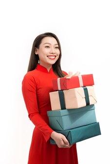 Schönen tet-urlaub. lächeln sie asiatische frau in ao dai, die geschenkbox des neuen jahres hält.