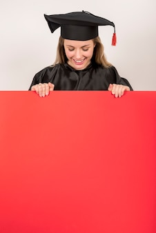 Schöner absolvent, der rotes plakatmodell hält