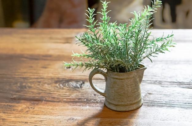 Schöner adlerfarn in einer vase wird auf einen holztisch gelegt.