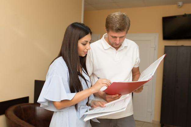 Schöner administrator der jungen frau bei empfang mit dem mann, der im ordner mit papieren schaut.
