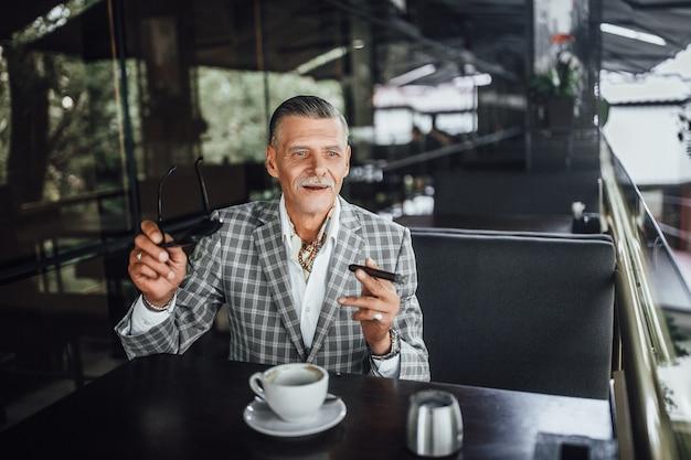 Schöner älterer mann, der seine frau an der sommerterrasse im modernen restaurant wartet.