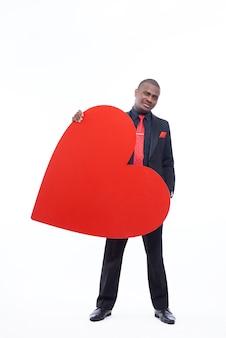 Schöner afrikanischer mann, der in der schwarzen suite und in der roten krawatte trägt, die großes rotes herz hält