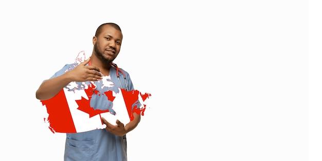 Schöner afroamerikanischer arzt kümmert sich um kanada über weißem studiohintergrund. exemplar. konzept des gesundheitswesens und der medizin, pflege, behandlung, diagnose während des ausbruchs des coronavirus.