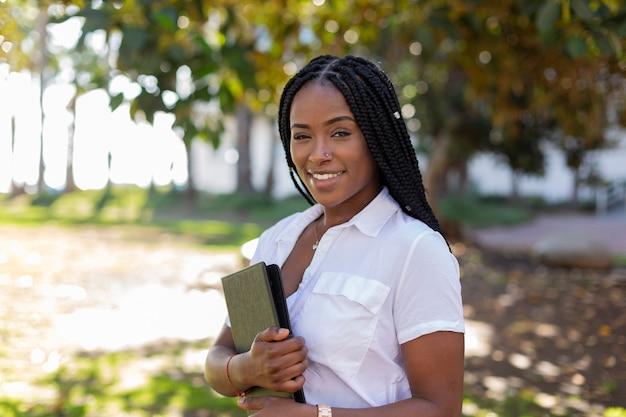Schöner afroamerikanischer student mit naturoberfläche. konzept für universitätsstudenten.